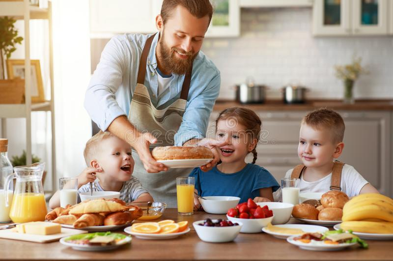 Happy family father with children feeds his sons and daughter in kitchen with Breakfast. Happy family father with many children feeds his sons and daughter in royalty free stock photos