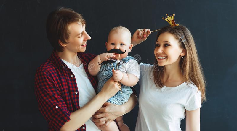 Happy family father mother and baby son on black background stock image