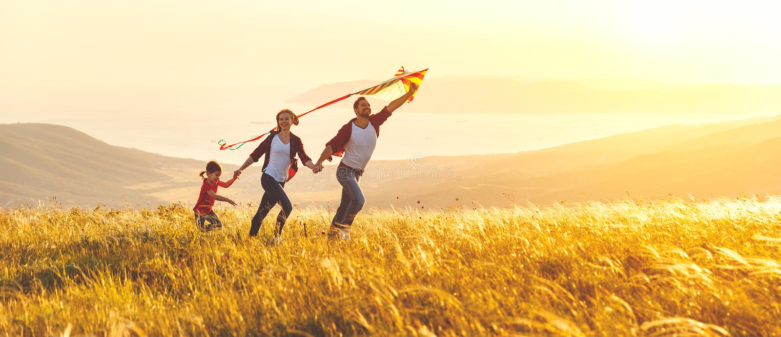 Happy family father, mother and child daughter launch a kite on stock photos