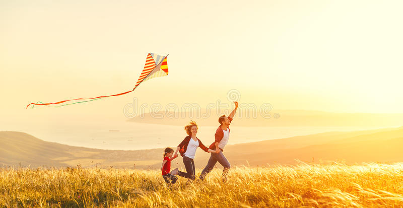 Happy family father of mother and child daughter launch a kite o. N nature at sunset