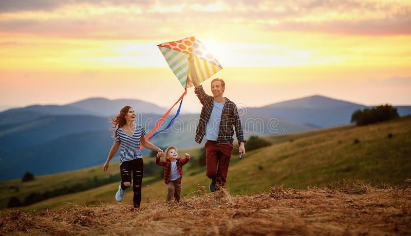 Happy family father of mother and child son launch a kite on nature at sunset royalty free stock photos