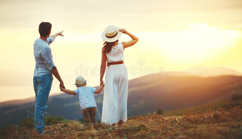Happy family father of mother and child son  on nature. At sunset royalty free stock image