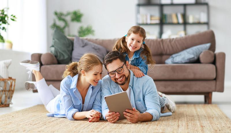 Happy family. father, mother and child with tablet computer at home stock photos