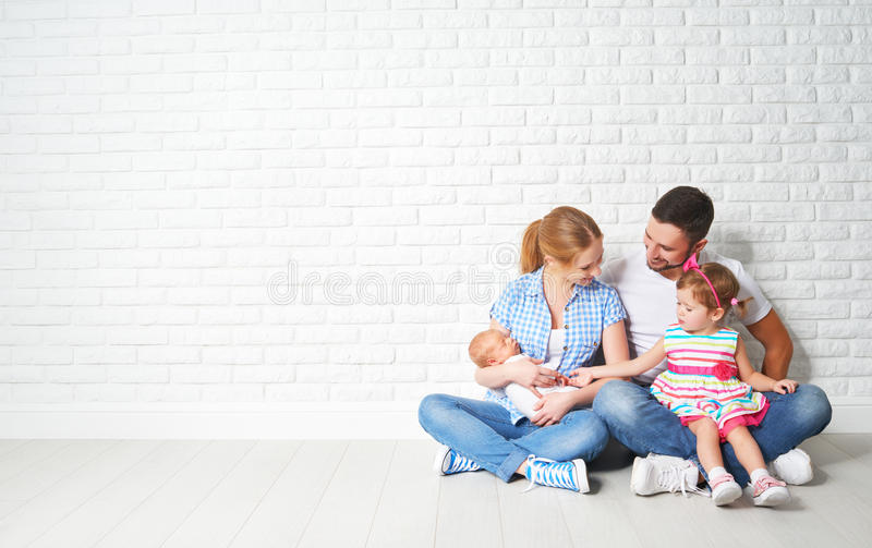 Happy family father mother and children at empty wall stock images