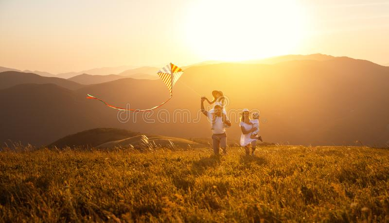 Happy family father, mother and children launch kite on nature. Happy family father, mother and children launch a kite on nature at sunset stock image