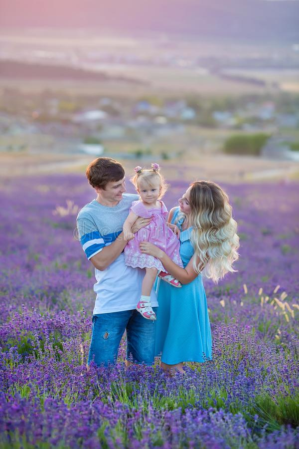 Happy family of father mother and daughter enjoy vacation on field of lavender flowers. Sensual scene of family happyness stock images