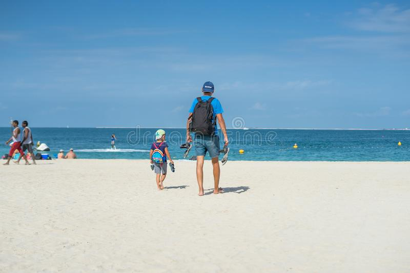 Happy family of father, mother and son goes vacation on a tropical sand beach in summer. Dubai beach royalty free stock photo