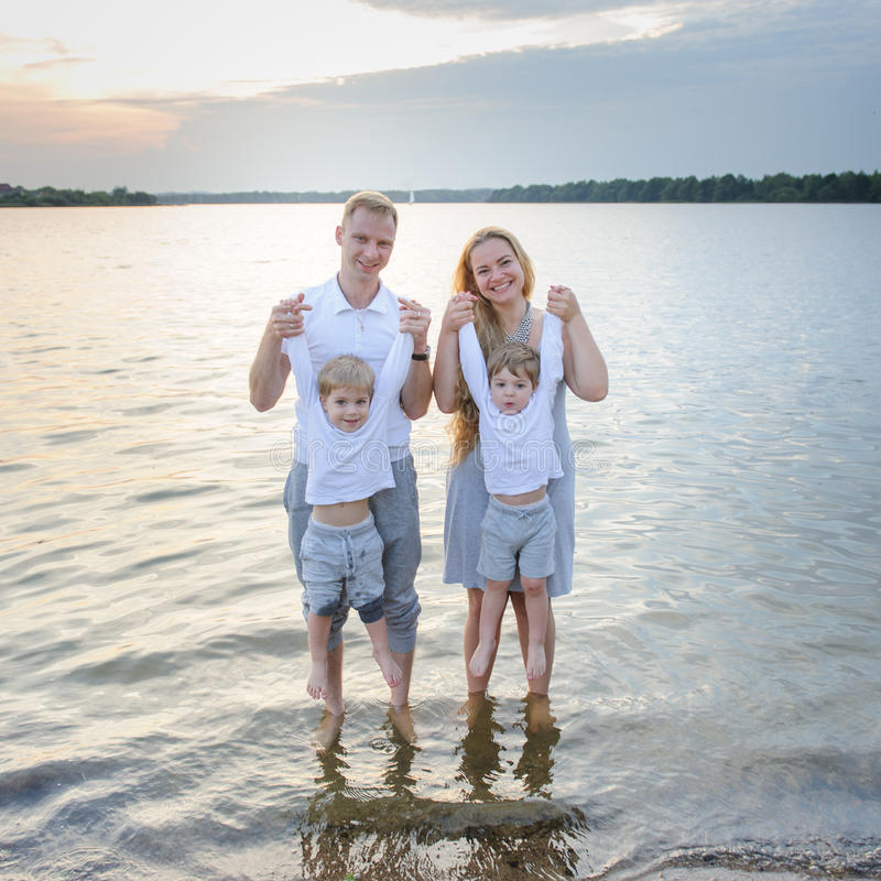 Happy family - father, mother, two sons on the beach with their feet in the water at sunset royalty free stock photos