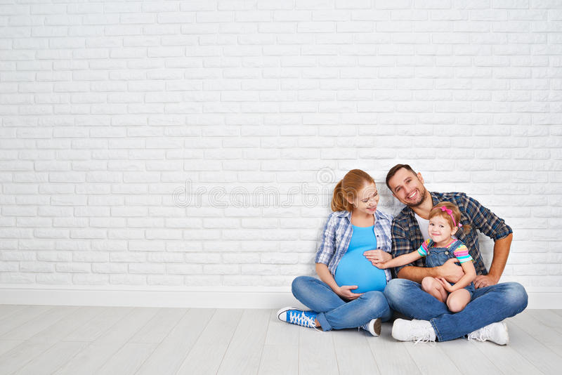 Happy family father and pregnant mother and child daughter near. A blank brick wall in the room stock images