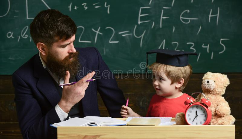 Happy family. Father and son doing homework together. Teacher in formal wear and pupil in mortarboard in classroom royalty free stock photography