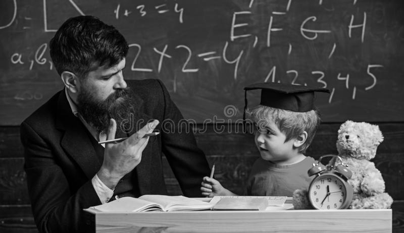 Happy family. Father and son doing homework together. Teacher in formal wear and pupil in mortarboard in classroom royalty free stock images