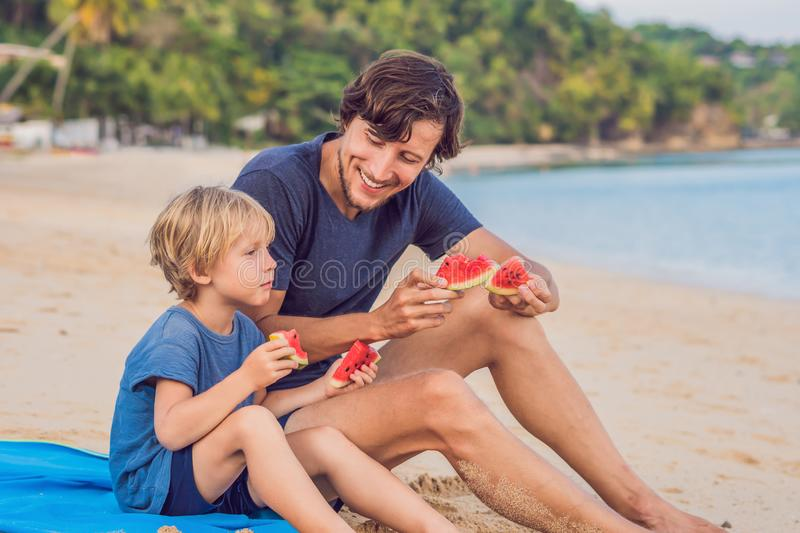 Happy family Father and son eating a watermelon on the beach. Children eat healthy food royalty free stock images