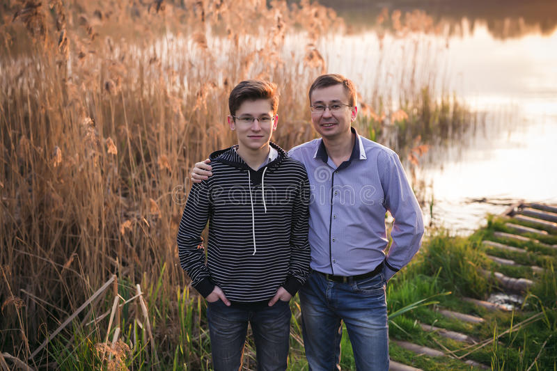 Happy family father with son posing on a background of a sunset on the river. Happy family father with son posing on a background of a beautiful sunset on the stock photos