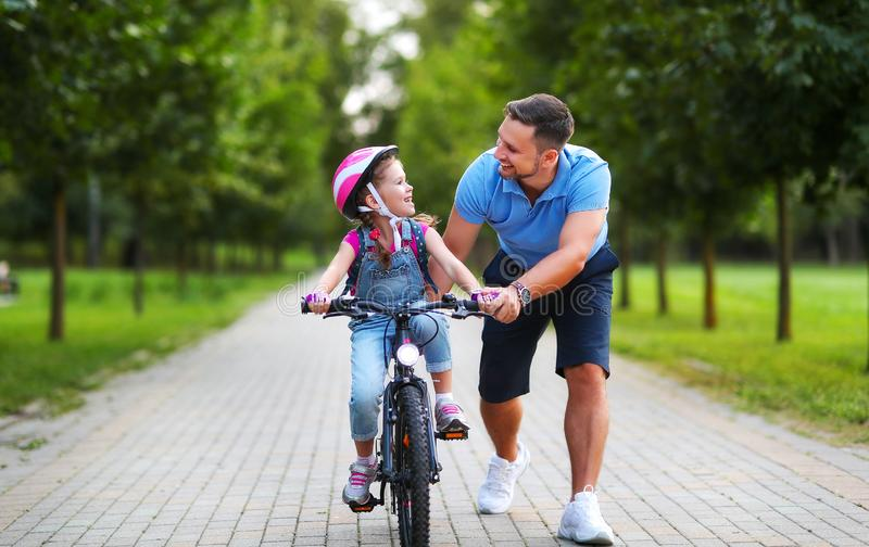 Happy family father teaches child daughter to ride a bike in the Park. In nature royalty free stock photo