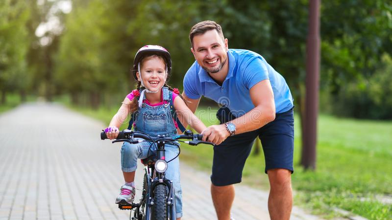 Happy family father teaches child daughter to ride a bike in the Park. In nature stock images