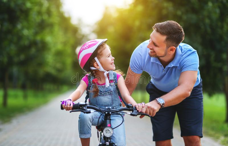 Happy family father teaches child daughter to ride a bike in the Park. In nature stock photo