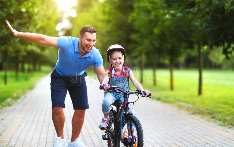 Happy family father teaches child daughter to ride a bike in the Park stock photo