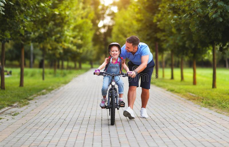Happy family father teaches child daughter to ride a bike in the Park royalty free stock photo