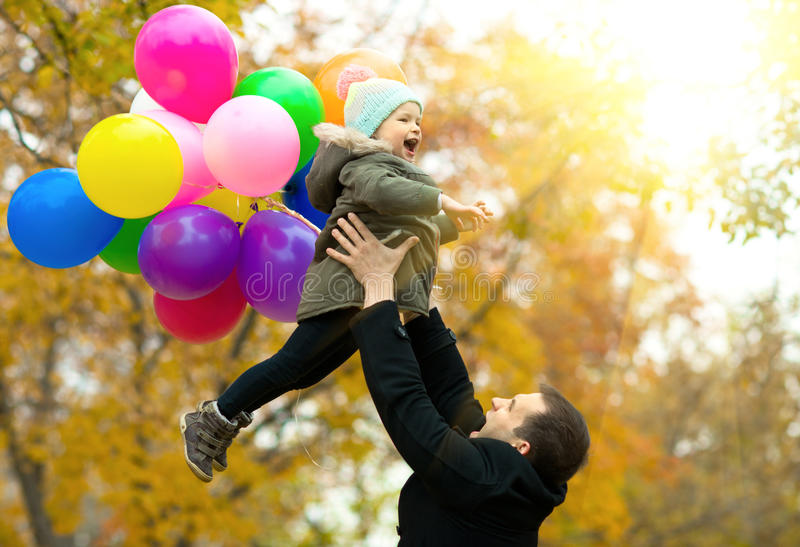 Happy family. Happy father toss up little child with air-balloons, outing in autumn park stock images