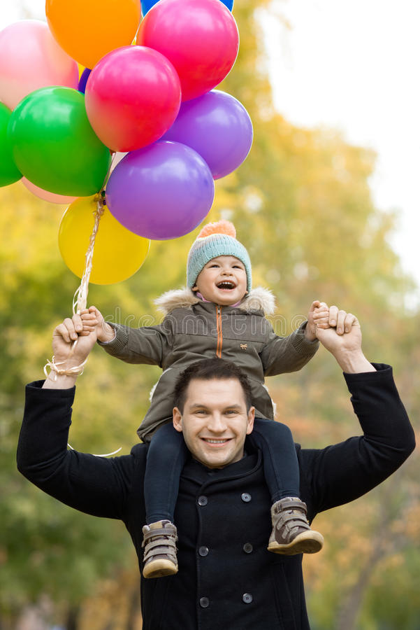 Happy family. Happy father toss up little child with air-balloons, outing in autumn park royalty free stock images