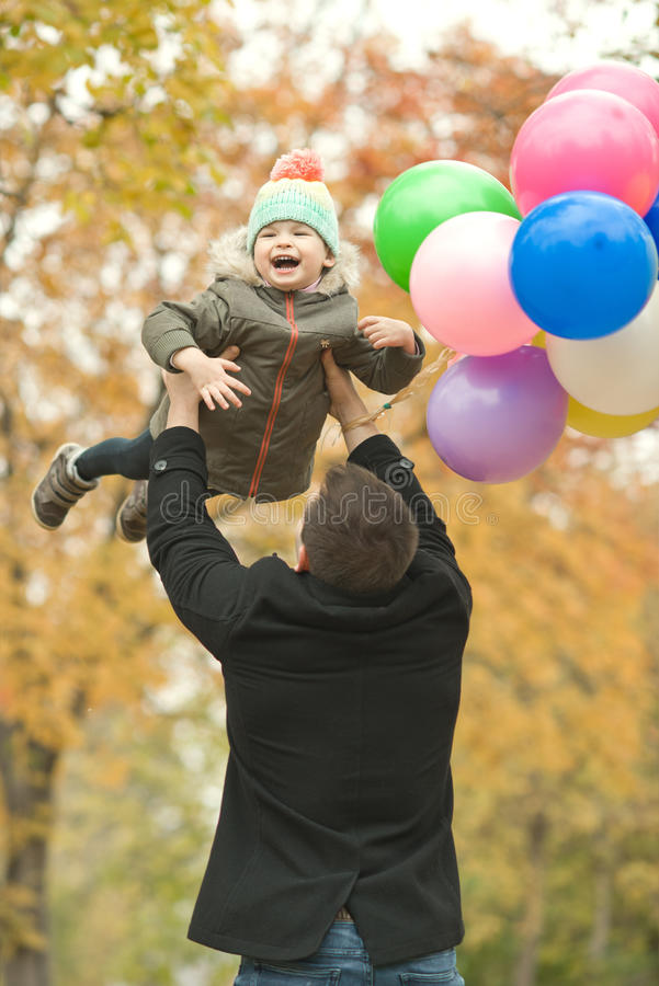 Happy family. Happy father toss up little child with air-balloons, outing in autumn park stock photos