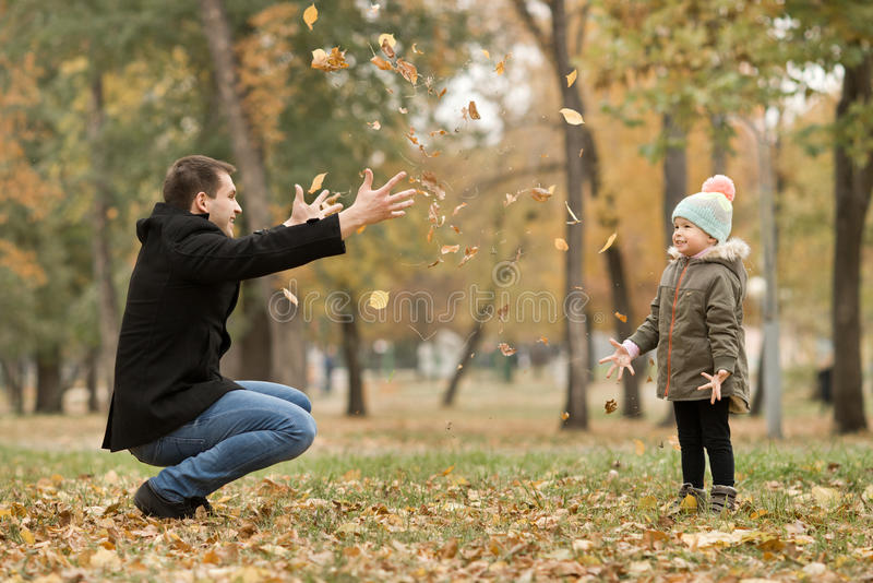 Happy family. Happy father toss up little child with air-balloons, outing in autumn park royalty free stock image