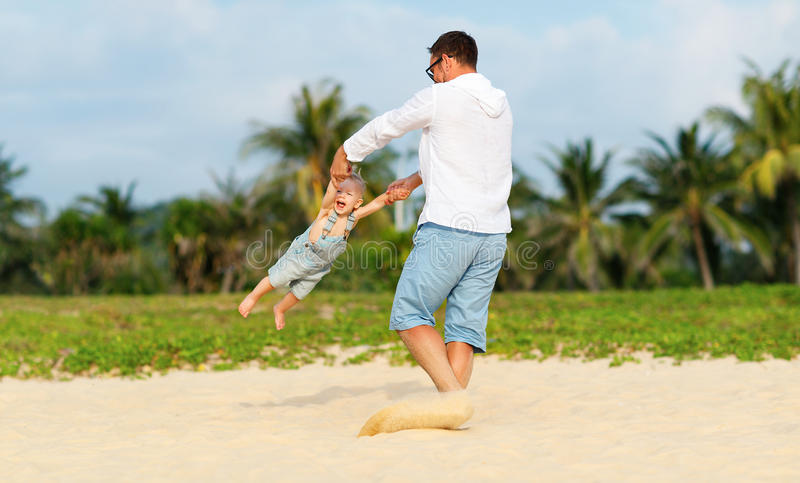 Happy family father turns baby son on beach. Happy family father turns baby son on the beach royalty free stock photography