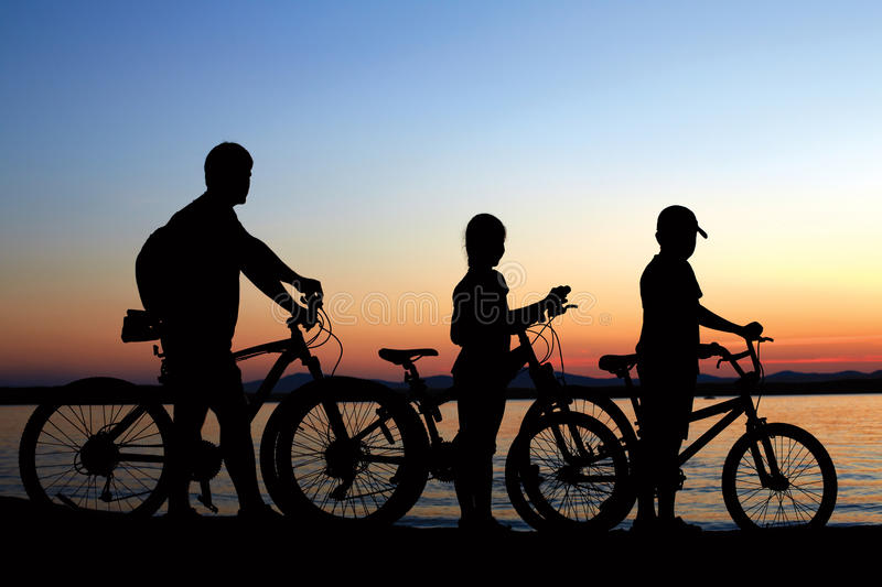 Happy family - father with two kids on bikes with dog stock image