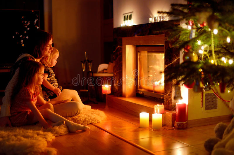 Happy family by a fireplace on Christmas. Young mother and her two little daughters sitting by a fireplace in a cozy dark living room on Christmas eve