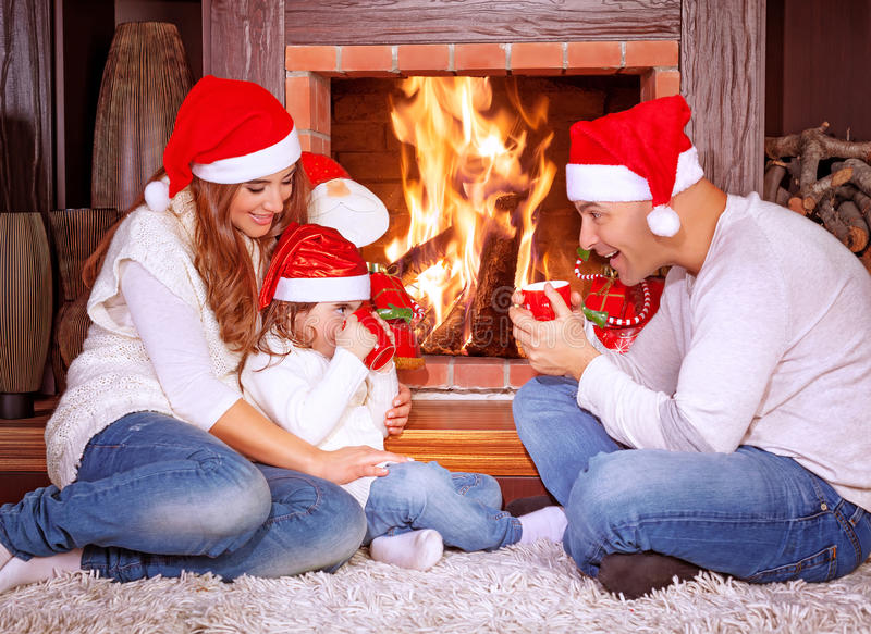 Happy family by fireplace. Parents with baby girl wearing Santa Claus hats, sitting relaxed in ski resort chalet and drinking hot tea, joyful winter vacation stock photos