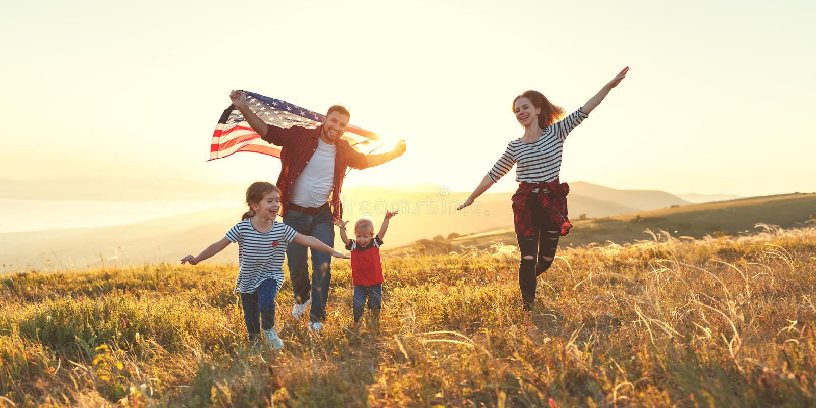 Happy family with flag of america USA at sunset outdoors royalty free stock photography