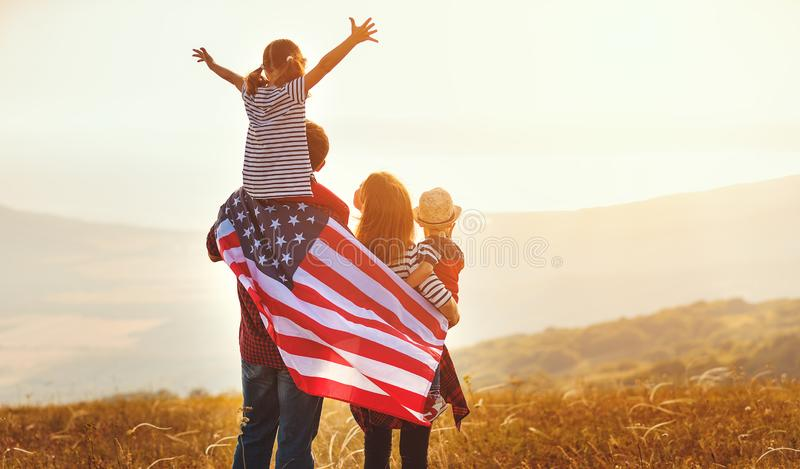 Happy family with flag of america USA at sunset outdoors. Happy family with the flag of america USA at sunset outdoors stock photography
