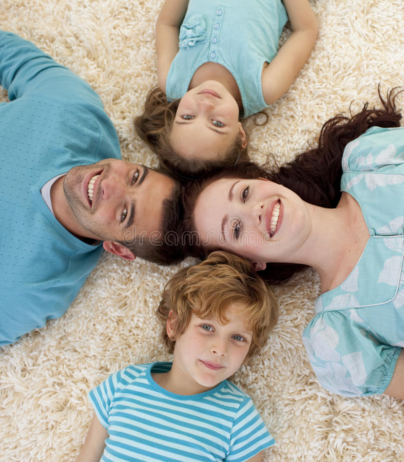Happy family on floor with heads together royalty free stock image