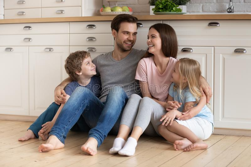Happy family of four sitting on wooden floor at kitchen. stock photography