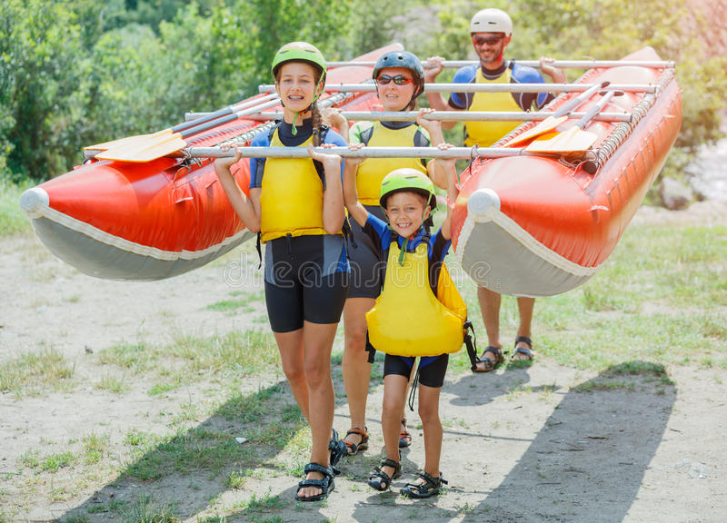 Happy family of four on the catamaran. Ready for rafting. Happy family of four wearing life vests and helmets on the catamaran. Rafting family on holidays royalty free stock image