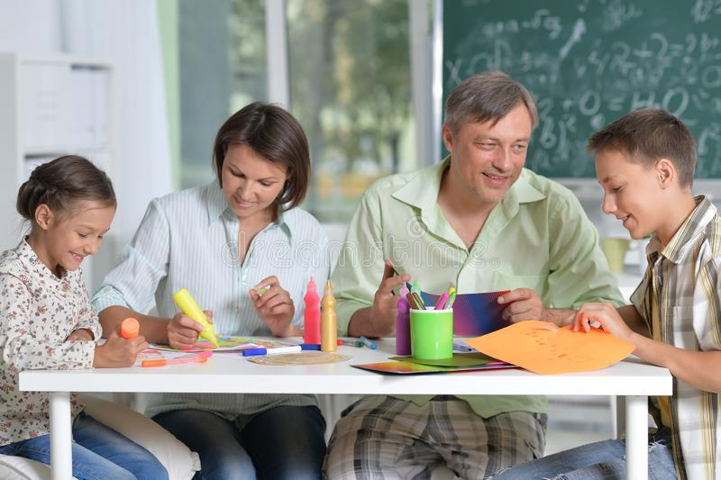 Portrait of happy family of four drawing together at home. Happy family of four drawing together at home royalty free stock photography