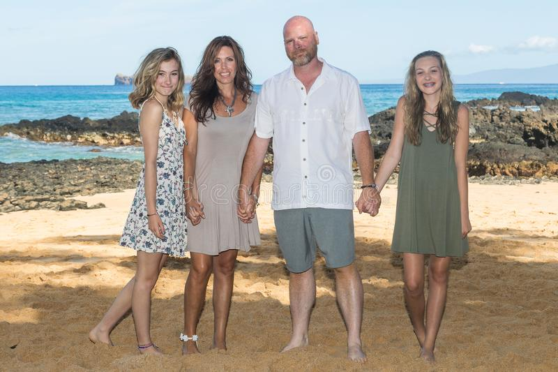 Happy Family together at the beach. Happy family of four on a Hawaiian vacation royalty free stock photography