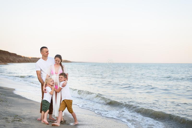 Happy family of four hugging on the sea coast. Parents, pregnant mother and two sons royalty free stock photo
