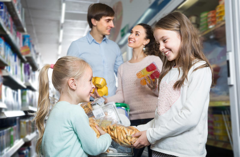 Happy family of four in hypermarket. Middle-class happy family of four doing shopping in hypermarket stock photo