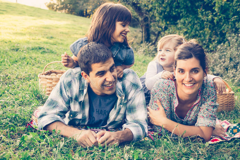 Happy family of four lying in the grass in autumn. After picking apples. Warm effect added royalty free stock image