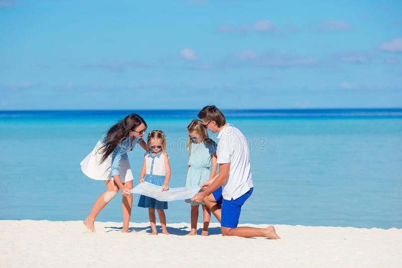 Happy young family of four with map on the beach royalty free stock image
