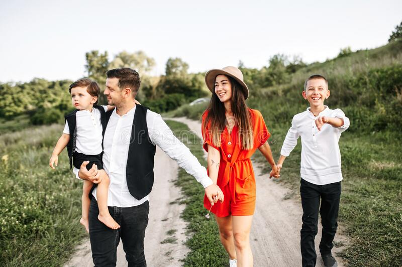 Happy family of four members walking through field. They are walking and holding hands, the youngest kid sits on father`s hand. Family is wearing casual smart royalty free stock photography