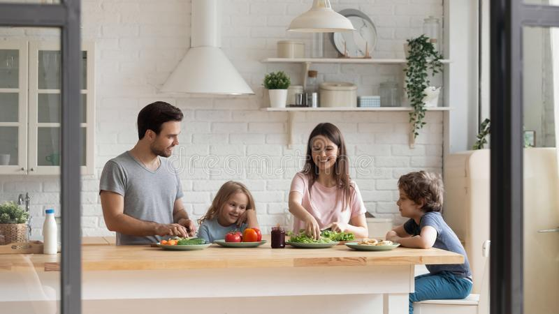 Happy family of four preparing healthy food together at kitchen. stock image