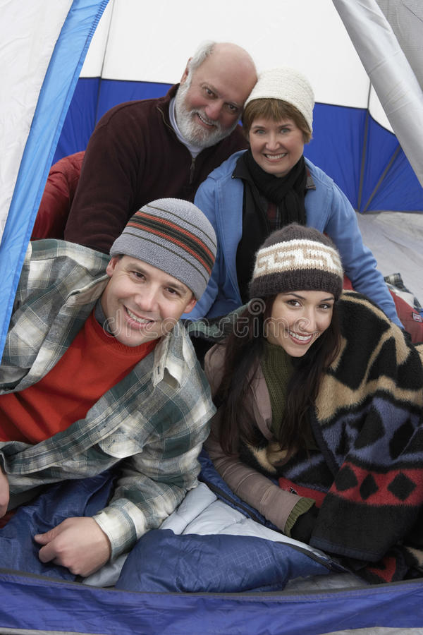Happy Family Of Four Relaxing In Tent. Portrait of happy family of four relaxing in tent while camping stock photos