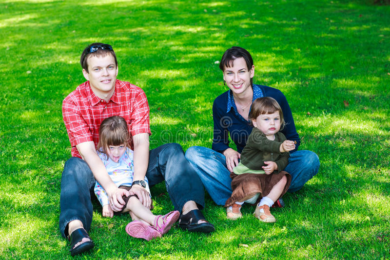 happy family of four sitting on grass stock images