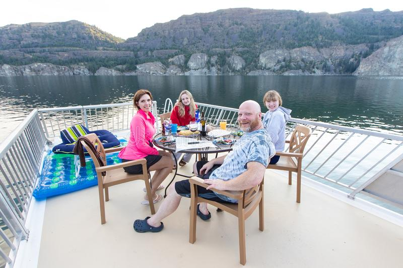 Happy family of four sitting together outside at a lake eating dinner royalty free stock image