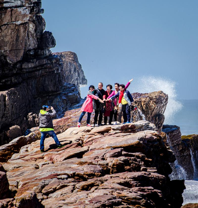 Happy family and friends posing for camera at world famous landmark. Cape of Good Hope, South Africa, 5 October 2017. Group of tourists at famous world landmark stock photo