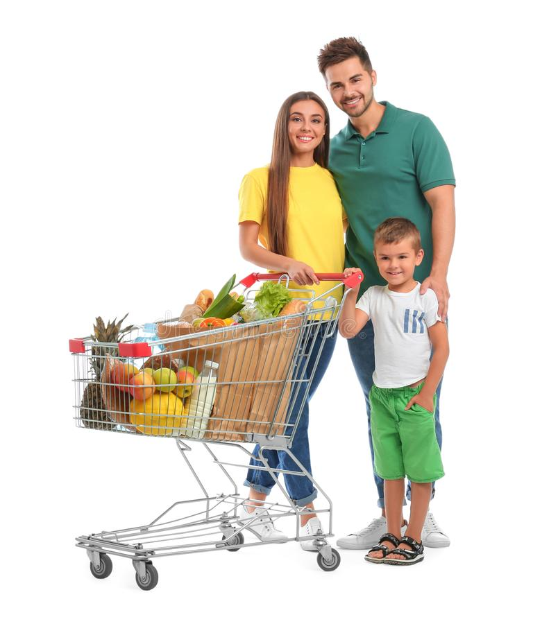 Happy family with full shopping cart on background. Happy family with full shopping cart on white background royalty free stock photo