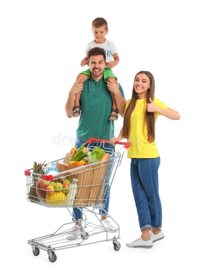 Happy family with full shopping cart on background. Happy family with full shopping cart on white background royalty free stock image