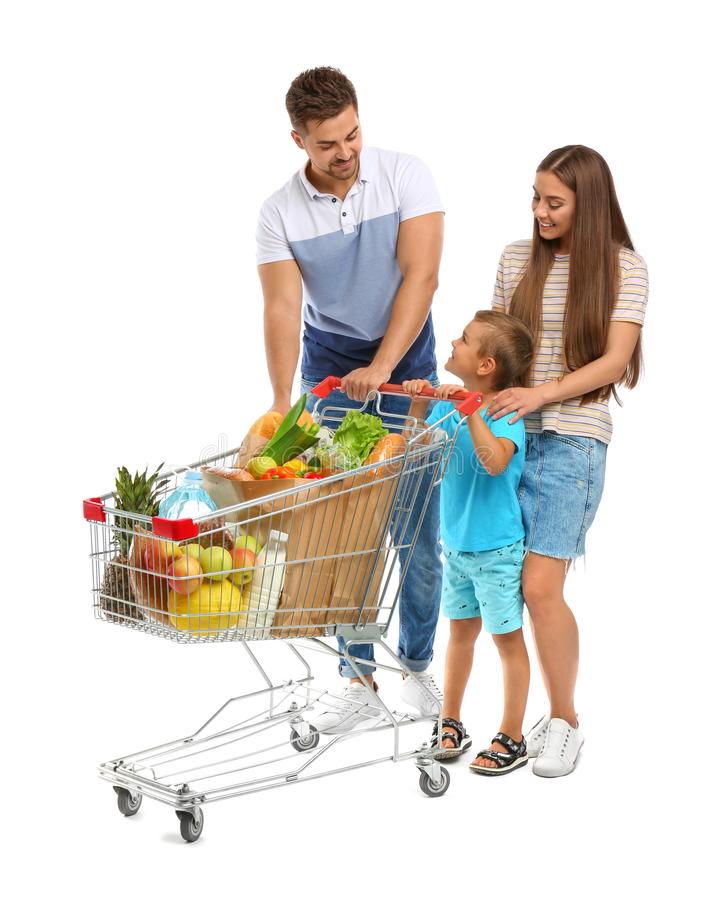 Happy family with full shopping cart on background. Happy family with full shopping cart on white background royalty free stock images